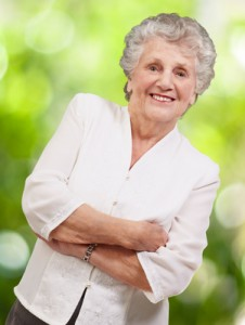 portrait of a adorable senior woman standing against a nature ba