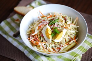 Light coleslaw salad with hard boiled egg, scallions and apples